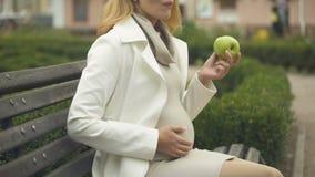 Senhora grávida loura que come a maçã verde, relaxando no banco, felicidade de maternidade filme