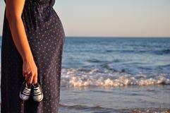 Senhora grávida pelo mar com sapatas de bebê Foto de Stock
