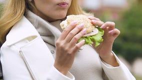 Senhora grávida que come o hamburguer com apetite saudável do presunto e da salada fresca, hora do almoço filme