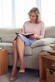 Senhora graciosa da letra de escrita da idade 30-40 ao sentar-se no sof Foto de Stock