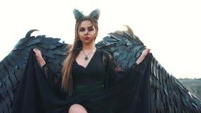A senhora graciosa em um vestido preto longo com luvas do la?o deixa cair a bainha do vestido, um anjo escuro com as asas fortes  vídeos de arquivo
