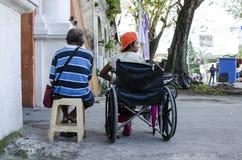 Senhora, homem cego ao lado do mendigo deficiente na cadeira de rodas no portal da porta da jarda da igreja para procurar a esmol fotografia de stock