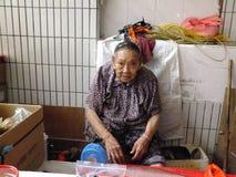 A senhora idosa chinesa mais do que e das pessoas de 90 anos, venda dos bens no mercado Fotos de Stock Royalty Free