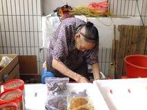 A senhora idosa chinesa mais do que e das pessoas de 90 anos, venda dos bens no mercado Imagens de Stock