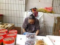 A senhora idosa chinesa mais do que e das pessoas de 90 anos, venda dos bens no mercado Imagem de Stock Royalty Free