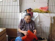A senhora idosa chinesa mais do que e das pessoas de 90 anos, venda dos bens no mercado Foto de Stock