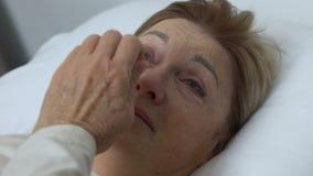 Senhora idosa de grito que encontra-se na cama em casa, na depressão, na vida e nos problemas de saúde vídeos de arquivo