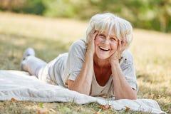 Senhora idosa de sorriso que coloca na grama Fotografia de Stock