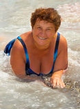 A senhora idosa feliz em uma praia, na água Imagens de Stock Royalty Free