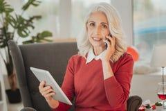Senhora idosa que fala no telefone celular e que descansa com tabuleta imagens de stock royalty free