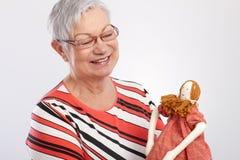 Senhora idosa que joga com sorriso da boneca de pano Fotografia de Stock