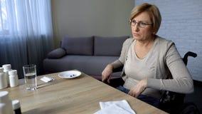A senhora idosa que senta-se na cadeira de rodas na tabela sente só e deprimida, lar de idosos imagem de stock