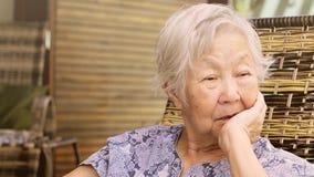 Senhora idosa só assentada em casa, com a mão no queixo com uma expressão triste video estoque