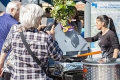 A senhora idosa toma fotos em seu telefone celular imagem de stock