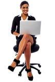 Senhora incorporada que trabalha em seu portátil Fotos de Stock