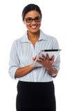 Senhora incorporada que trabalha no dispositivo da tabuleta Fotografia de Stock Royalty Free