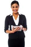 Senhora incorporada que trabalha no dispositivo da tabuleta Fotografia de Stock