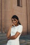 Senhora indiana flertando no vestido branco contra a construção antiga Imagens de Stock