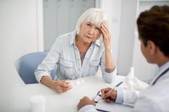 Senhora infeliz que tem a dor de cabeça e que senta-se na frente do doutor imagens de stock