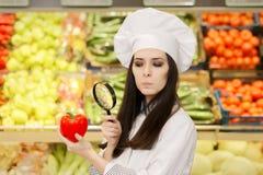 Senhora interessada Cozinheiro chefe Inspecting Vegetables com lupa Imagens de Stock Royalty Free