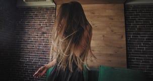 Senhora longa do cabelo muito consideravelmente com um sorriso bonito na frente da câmera que joga a dança carismática e que sent vídeos de arquivo