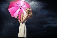 Senhora loura alegre com o guarda-chuva cor-de-rosa Imagens de Stock