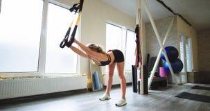 Senhora loura bonita exercícios de resistência totais praticando TRX do corpo para treinar seu estilo de vida magro e do músculo  filme