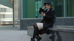 A senhora loura bonita no chap?u negro que o vestido branco apertado levanta o assento no banco olha para cima contra a constru?? video estoque