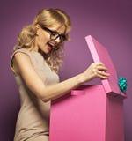 Senhora loura encantador que abre uma caixa de presente Fotografia de Stock
