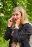 Senhora loura nova que fala através do telefone móvel Imagens de Stock Royalty Free