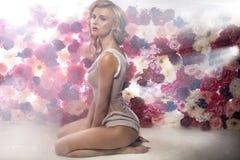 Senhora loura sensual entre as flores das centenas Imagem de Stock