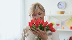 Senhora loura superior que aspira o ramalhete das tulipas que olha in camera, presente do feriado vídeos de arquivo