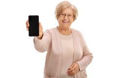 Senhora madura alegre que mostra um telefone fotografia de stock