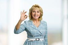 Senhora madura de sorriso que mostra a aprovação do sinal foto de stock