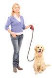 Senhora madura que guarda um cão em uma trela Imagem de Stock