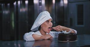 A senhora magro e impressionante nova do padeiro tomou a cereja fora do bolo de chocolate e pô-la em sua boca que ri alegremente vídeos de arquivo