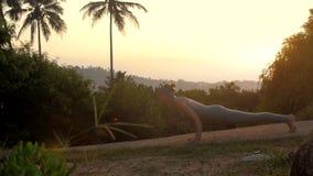 A senhora magro faz a pose da ioga da saudação do sol no movimento lento da trilha vídeos de arquivo
