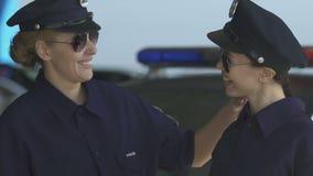 Senhora mais idosa da polícia que incentiva o colega novo, sorrindo e olhando à came video estoque