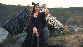Senhora misteriosa no vestido leve preto do la?o com trem longo, menina com p? aberto nas botas de couro, anjo horned escuro de filme