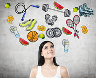 A senhora moreno bonita contemplativo está pensando sobre sua escolha da atividade do esporte Os ícones coloridos do esporte são  Imagens de Stock