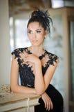 Senhora moreno bonita no vestido preto elegante do laço que levanta em uma cena do vintage Mulher elegante sensual nova fotografia de stock royalty free