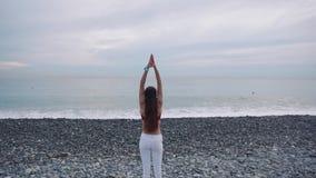 A senhora moreno está relaxando o mar de observação, posição e está meditando sobre a praia video estoque