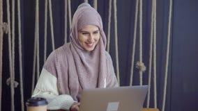 A senhora muçulmana alegre está lendo mensagens no caderno, está sorrindo e está escrevendo a resposta video estoque