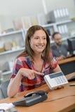 Senhora na mesa que aponta para indicar na calculadora imagens de stock
