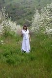 Senhora no branco entre árvores de florescência Fotografia de Stock Royalty Free