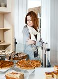 Senhora no lenço que olha o exemplo de vidro da padaria Fotografia de Stock Royalty Free