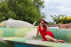 Senhora no vermelho na asa do avião do vintage fotografia de stock royalty free