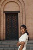 Senhora no vestido contra a construção antiga com olhar pensativo Foto de Stock Royalty Free