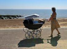 Senhora no vestido que empurra o Pram antiquado ao longo do passeio da frente marítima Foto de Stock Royalty Free