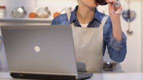 Senhora no vinho bebendo do avental, escolhendo na receita em linha do portátil cozinhar o jantar video estoque